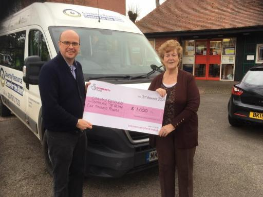 Hugh Sorrill and Rosie Brady receive cheque in front of minibus